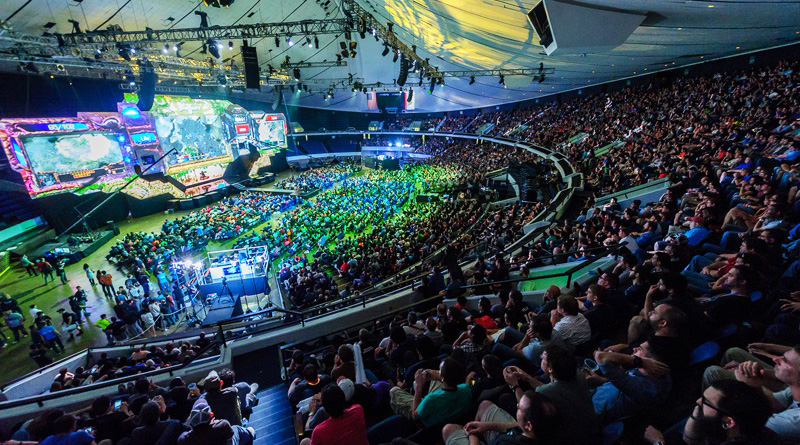 FIFA Esports In Asia: Why do gamers have two headsets? a large stadium packed with people. Green, blue, and yellow strobe lights illuminate the stadium, which focuses on a large screen that shows the esports pro gamers playing a game.